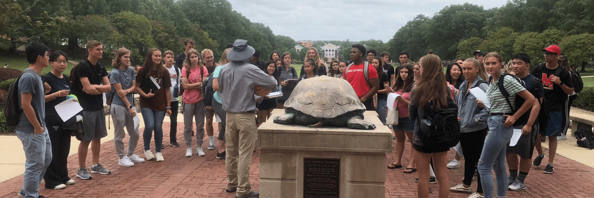 group of students face Testudo statue and professor in safari outfit